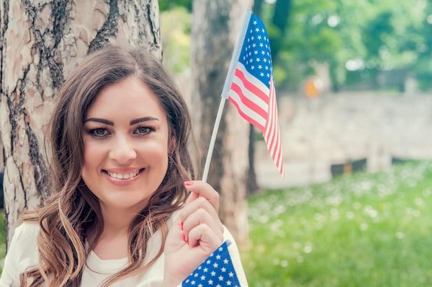 Schöne patriotische junge frau mit der amerikanischen flagge