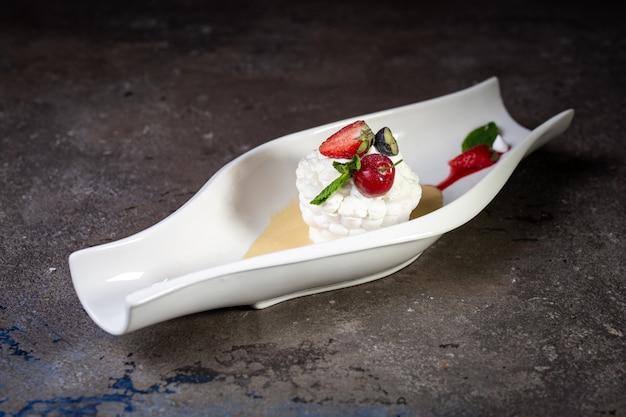 Schöne pavlova-kuchen mit erdbeeren auf einem weißen teller