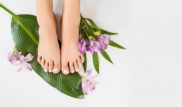 Schöne perfekte weibliche füße draufsicht mit tropischen blumen und grünem palmblatt