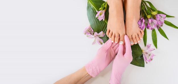 Schöne perfekte weibliche hautbeinefüße draufsicht mit tropischen blumen und grünem palmblatt