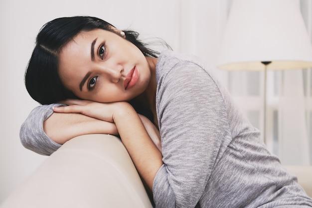 Schöne philippinische frau, die sich zurück auf sofa lehnt