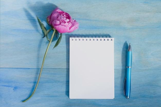 Schöne pion, stift, notizblock auf blauem grund. platz kopieren