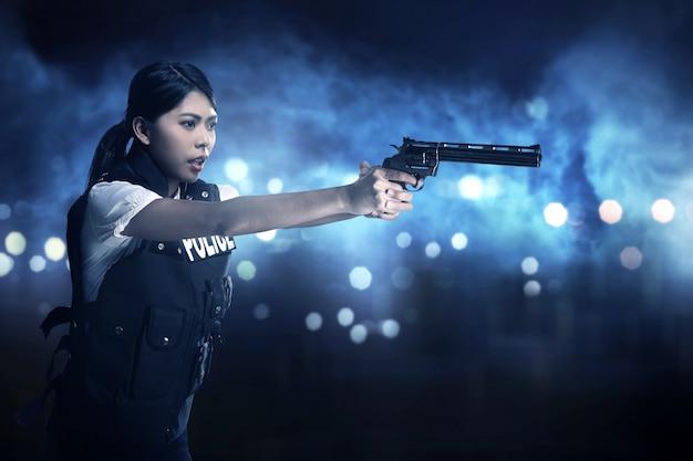 Schöne polizistin, die gewehr hält