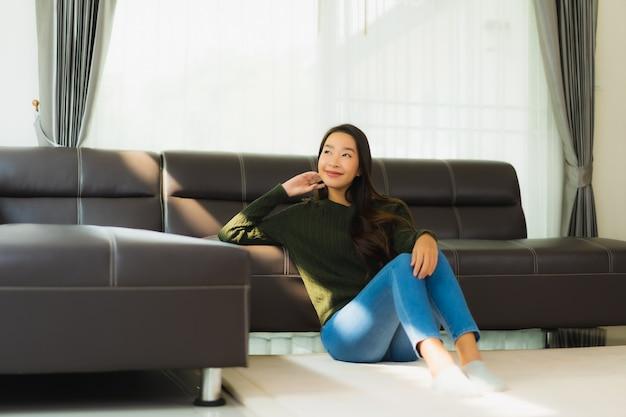 Schöne porträt junge asiatische frau sitzen entspannen auf dem sofa