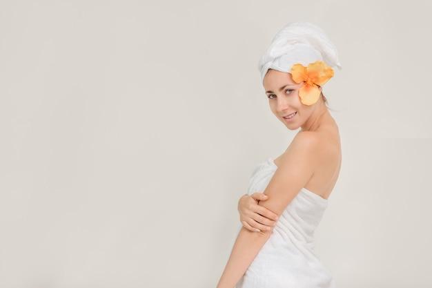 Schöne porträtbadekurortfrau, die jugend und hautpflege-konzept aufwerfend steht