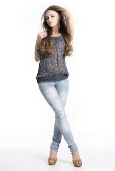 Schöne posierende junge frau in jeans - lokalisiert auf weißem hintergrund. porträt in voller länge