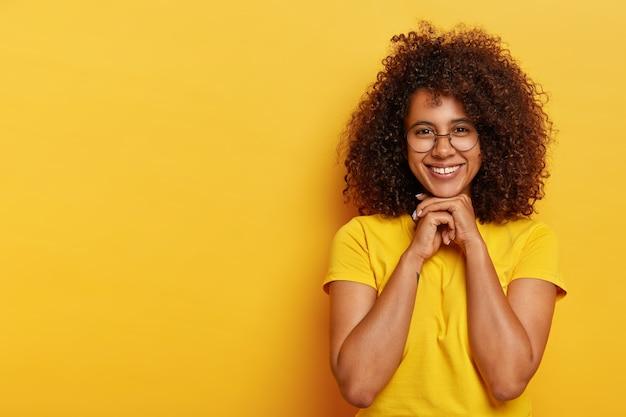Schöne positive afro-frau hat lockiges haar, gesunde haut, hält die hände unter dem kinn zusammen, freut sich über angenehme kommentare zu ihrer arbeit, trägt ein gelbes t-shirt, modelle im innenbereich. konzept der menschlichen emotionen