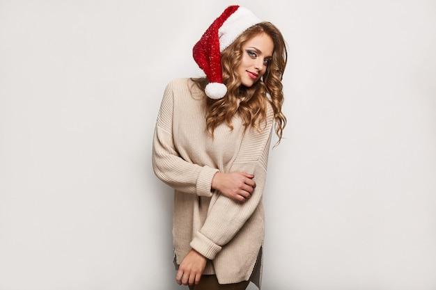 Schöne positive blondine in einer strickjacke und in einer festlichen kappe