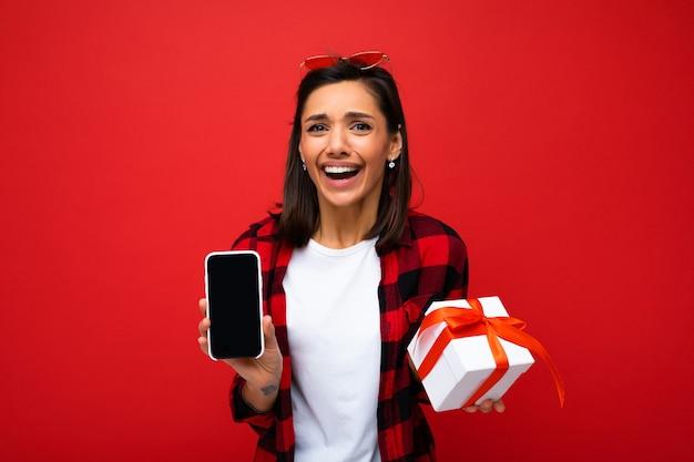 Schöne positive erstaunte junge brunet-frau isoliert über roter hintergrundwand mit weißem casual-t-shirt und rotem und schwarzem hemd mit weißer geschenkbox mit rotem band und handy mit leerem d