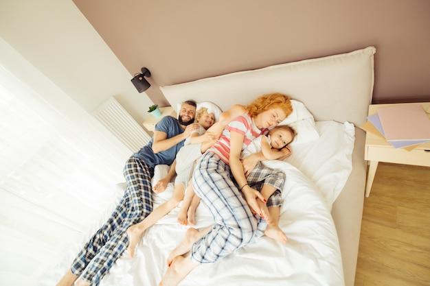 Schöne positive familie, die zusammen im bett schläft