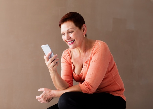 Schöne positive frau mit dem telefonlachen