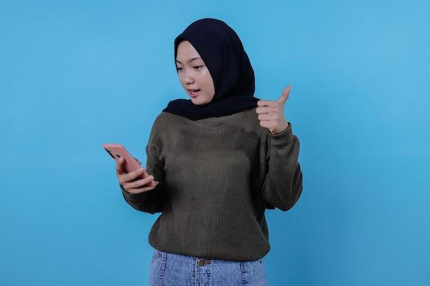 Schöne positive, freundlich aussehende junge frau, die hijab mit einem schönen aufrichtigen lächeln trägt und sich dankbar und dankbar fühlt, das handy zu halten