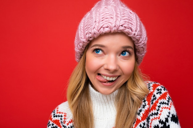 Schöne positive glückliche junge blonde frau lokalisiert über bunter hintergrundwand, die lässig trägt
