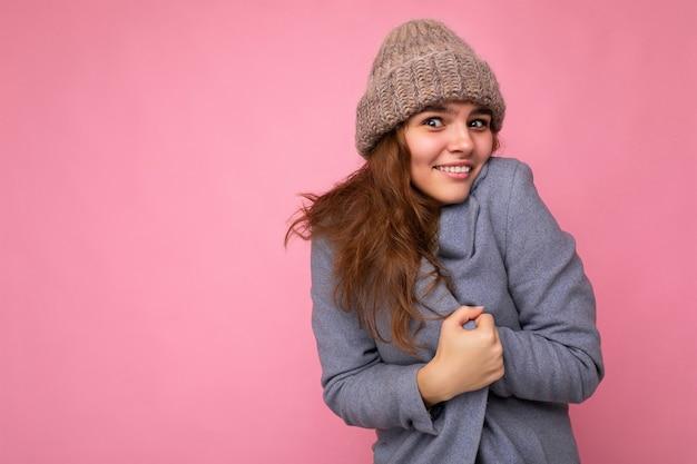 Schöne positive glückliche junge brünette frau lokalisiert über bunter hintergrundwand, die lässig trägt