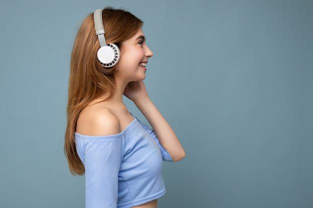 Schöne positive lächelnde junge blonde frau des seitenprofils, die das blaue erntedach isoliert trägt