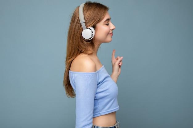 Schöne positive lächelnde junge blonde weibliche person des seitenprofils, die blaues bauchfreies top trägt wearing