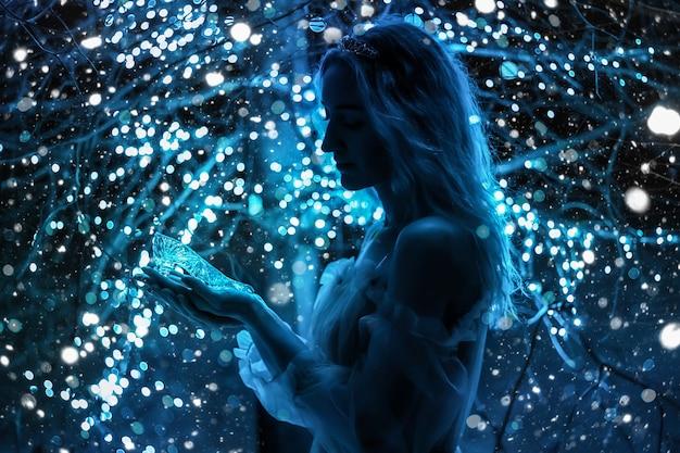 Schöne prinzessin im blauen langen kleid auf dem leuchtenden baumhintergrund mit kristallschuh in der hand. kunstverarbeitung.