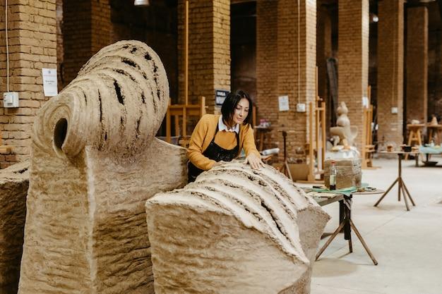 Schöne professionelle bildhauerin mittleren alters, die an einer wunderschönen skulptur arbeitet. Premium Fotos