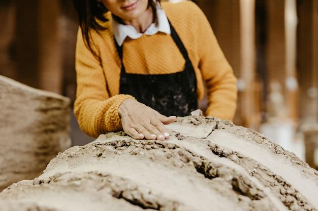 Schöne professionelle bildhauerin mittleren alters, die an einer wunderschönen skulptur arbeitet.