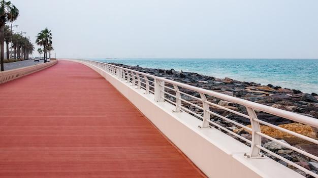 Schöne promenade mit gehweg und weißem zaun.
