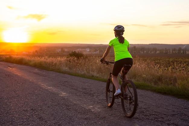 Schöne radfahrerin, die ein fahrrad auf der straße gegen sonnenuntergang reitet. natur und erholung. hobbys und sport