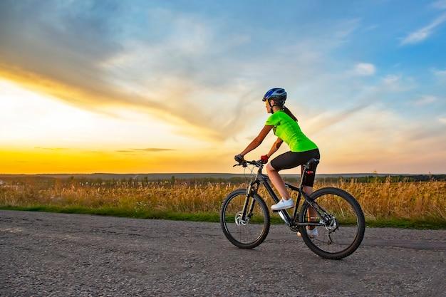 Schöne radfahrerin, die ein fahrrad auf der straße in richtung sonnenuntergang reitet