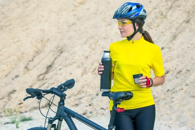 Schöne radfahrerin in gelb mit tee und thermoskanne in der hand