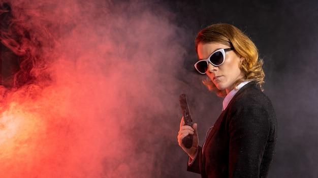 Schöne raue elegante frau mit pistole in der hand. rauch und feuer auf dunklem hintergrund.