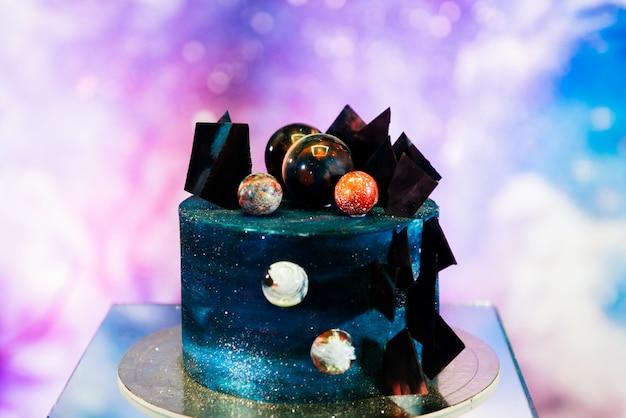 Schöne raumhochzeitstorte verziert mit schokolade und planeten. das konzept der feiertagsdesserts für einen geburtstag, feiertag