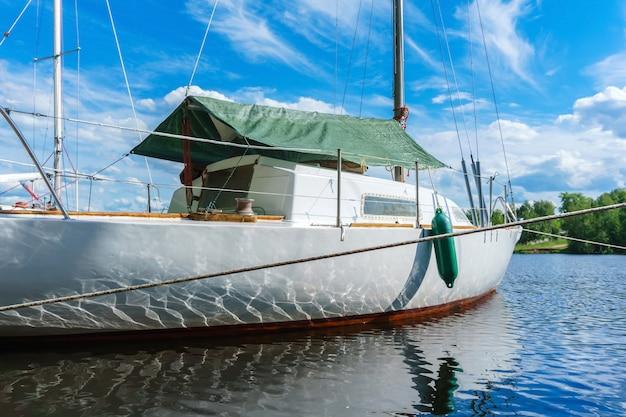 Schöne reflexionen von wellen und sonnenlicht an bord eines kleinen segelboots, das in einer bewaldeten bucht vor anker liegt