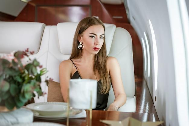 Schöne reiche frau in einem privaten flugzeug erster klasse
