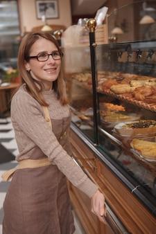 Schöne reife bäckerin lächelt und posiert stolz in ihrem eigenen bäckereigeschäft