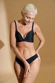 Schöne reife blonde frau mit fittem körper in schwarzer unterwäsche, die ihre körperhaut berührt, während