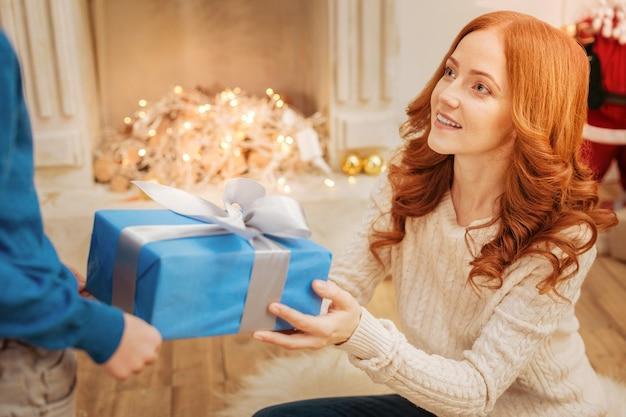 Schöne reife dame, die auf dem boden sitzt, während sie ihrem kleinen sohn ein weihnachtsgeschenk an einem festlichen morgen in einem familienkreis gibt.