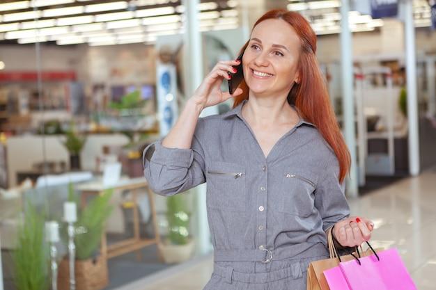 Schöne reife frau, die am telefon spricht, im einkaufszentrum spazieren geht, raum kopiert. lebensstil, kommunikationskonzept