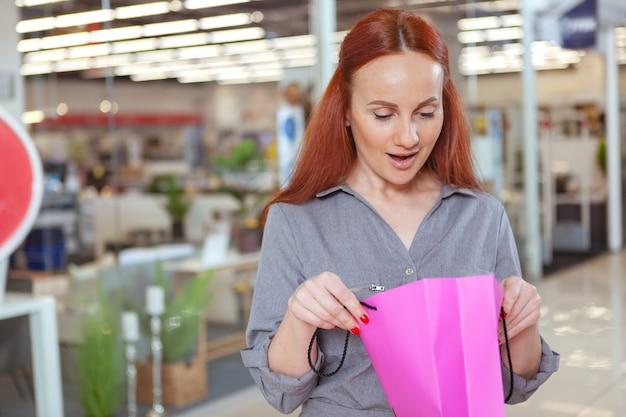 Schöne reife frau, die aufgeregt schaut und ihre einkaufstasche im einkaufszentrum öffnet. kundin, die in ihre einkaufstasche schaut