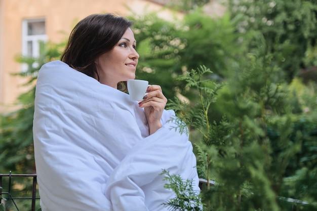 Schöne reife frau, die mit tasse kaffee entspannt