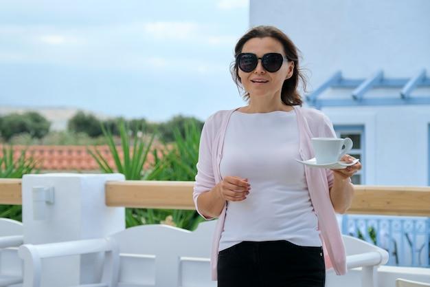 Schöne reife frau, die urlaub im resorthotel genießt, im restaurant, blick auf die berglandschaft. frau, die mit tasse kaffee geht. freizeit, sommer, wochenende, tourismus, reisen menschen mittleren alters