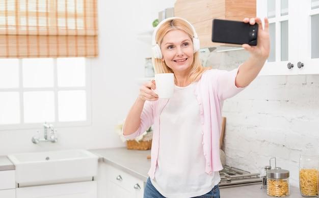 Schöne reife frau, die zu hause ein selfie nimmt