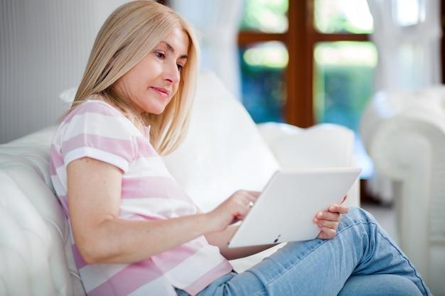 Schöne reife frau, die zu hause elektronische tablette verwendet