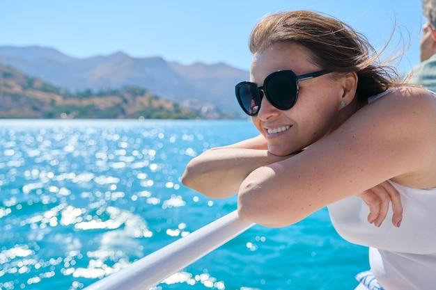 Schöne reife frau genießt sommer-seereise, weiblich auf der seite des kleinen vergnügungsboots