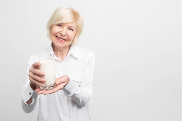 Schöne reife frau hält eine tasse milch und lächelt. es ist gut, es jeden tag zu trinken. tolle angewohnheit.