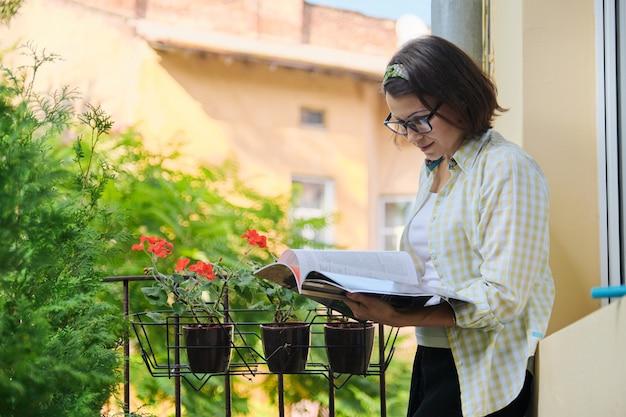 Schöne reife frau in der hauskleidung auf offenem balkon, der magazin liest
