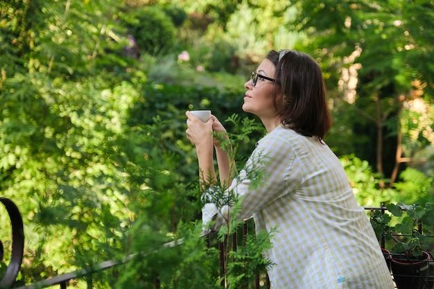 Schöne reife frau in der hauskleidung auf offenem balkon mit tasse kaffee Premium Fotos