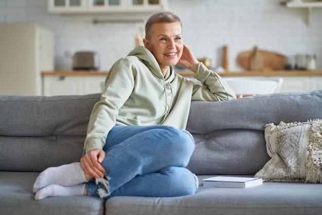 Schöne reife frau in freizeitkleidung, die von etwas träumt, während sie sich zu hause auf dem sofa entspannt