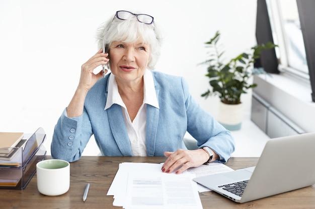 Schöne reife frau mit grauem haar, das telefonanrufe in ihrem büro, eleganter älterer weiblicher unternehmer im stilvollen anzug macht, der auf handy mit potentiellem partner spricht, am arbeitsplatz mit laptop sitzt