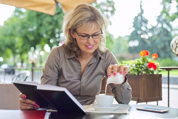 Schöne reife geschäftsfrau, die kaffee in der pause im restaurant im freien trinkt