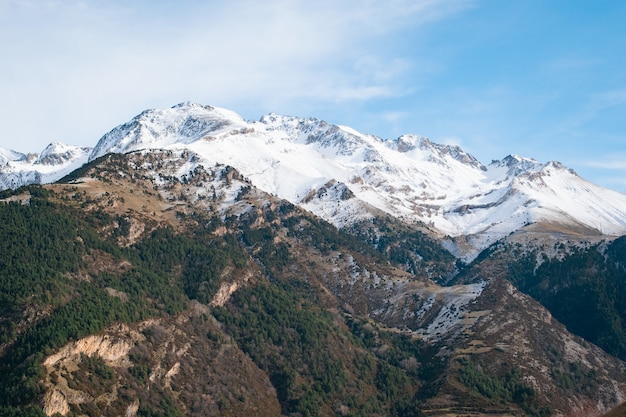Schöne reihe von hohen felsigen bergen, die tagsüber mit schnee bedeckt sind