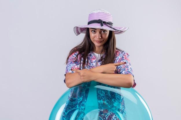 Schöne reisende frau, die sommerhut trägt, der mit aufblasbarem ring steht, der hände kreuzt und mit dem finger zu den seiten mit ernstem sicherem ausdruck über weißem ba zeigt