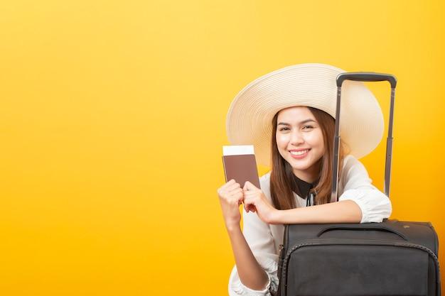 Schöne reisendfrau ist auf gelbem hintergrund aufregend